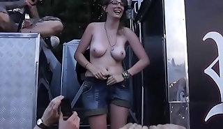 Cute girl shows boobs and ass on a festival stage